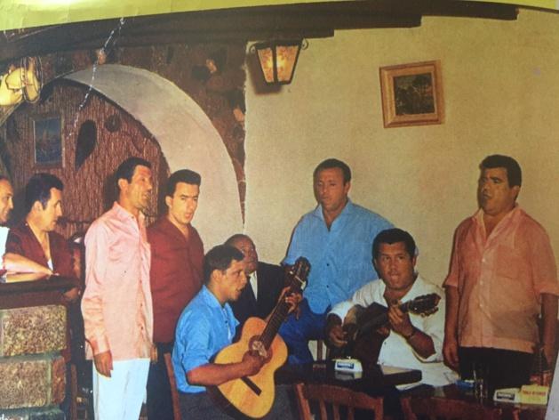 Marco, debout au centre, chemise bleue