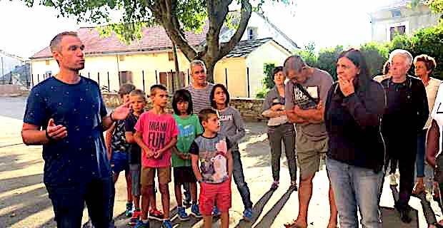 Pierre-Ange Mazzoni, délégué des parents d'élèves, entouré de parents et d'enfants dans la cour de récréation de l'école primaire de Murato.