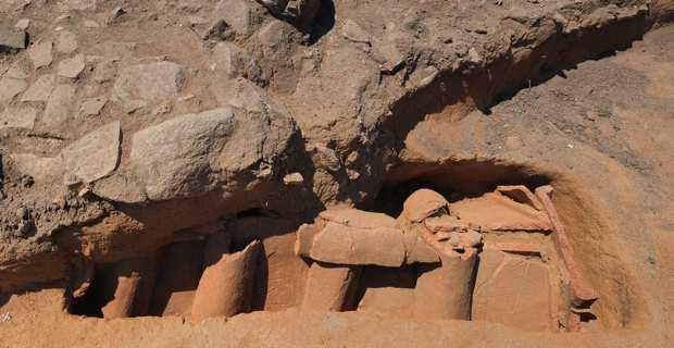 Tombe en bâtière décorée de symboles en traces digitées située sous l'empierrement. Photo Inrap.