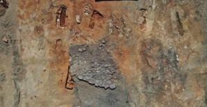 Empierrement en partie fouillé sous lequel apparaît la tombe en bâtière décorée. Photo Inrap.