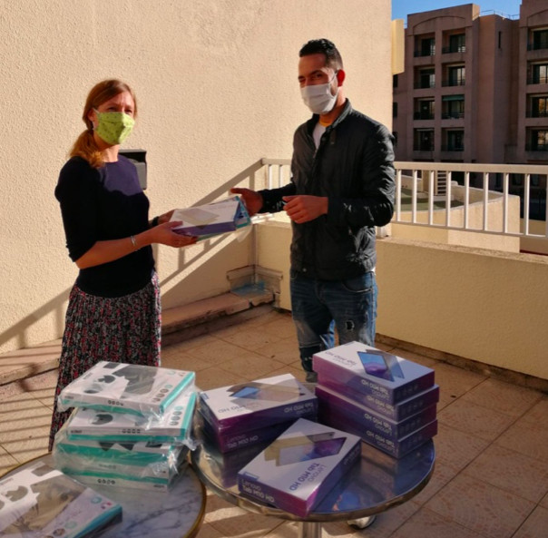 Laureline Roux remet une des tablettes offertes par la préfecture de Haute-Corse à un des parents bénéficiaires de ce don.