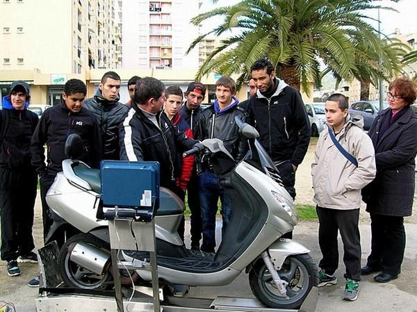"""Les jeunes participants ont pu prendre conscience des dangers liés à l'utilisation d'un deux-roues. Ici, Valère Duch souligne le risque lié au """"débridage"""" des machines à l'aide d'un curvomètre. (Photo : Yannis-Christophe Garcia)"""