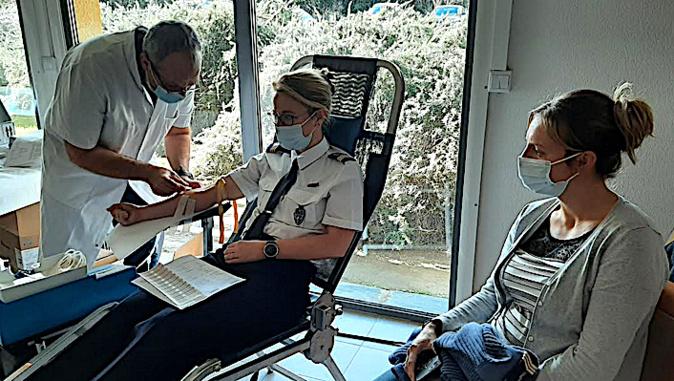 Raymond, l'infirmier de l'EFS, prépare le prélévement de Virginie sous le regard attentif d'Amandine