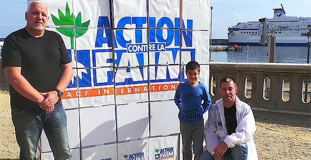 Jean-Marcel Vuillamier (à gauche) devant le mur d'action contre la faim