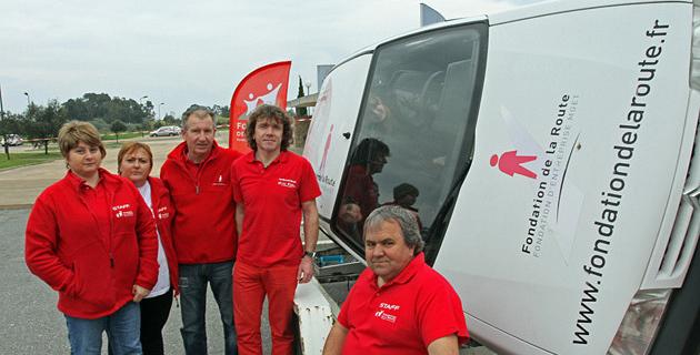 Les bénévoles de la fondation de la route et la voiture simulant les tonneaux. (Photo SG).