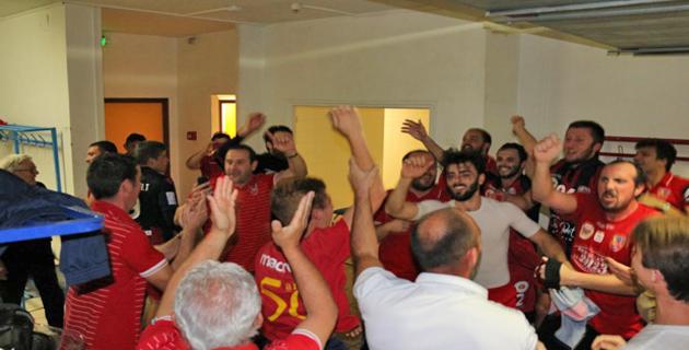 L'équipe et le staff fêtant la victoire dans les vestiaires.