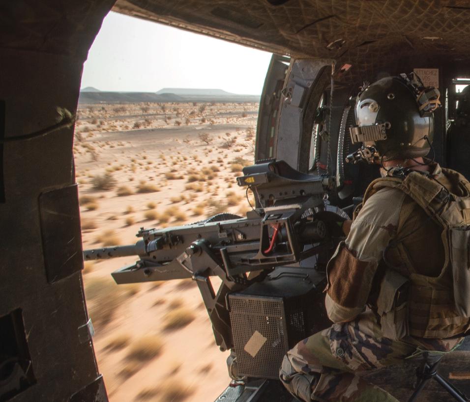 Dans les montagnes afghanes, un gunner assure la protection de l'hélicoptère (Photo ECPAD)