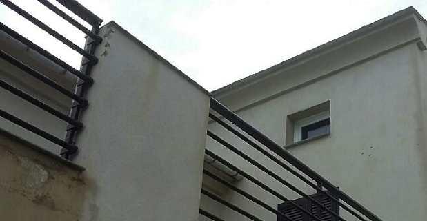 Impacts de balles sur la façade et la rembarde en fer.