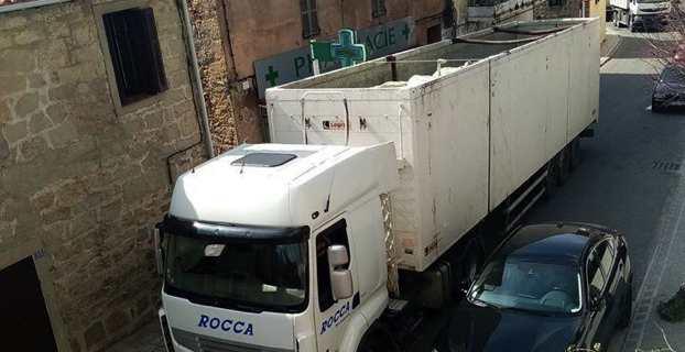 Un camion empli de balles de déchets et non bâché traverse le village d'Olmetu.