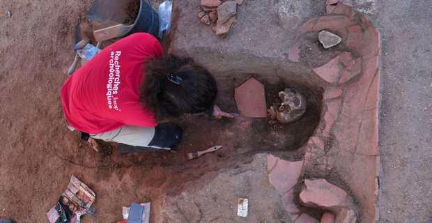 Une archéologue de l'Inrap est en train de fouiller une sépulture médiévale en pleine terre ayant recoupée une sépulture en amphore africaine antérieure. Photo Inrap.
