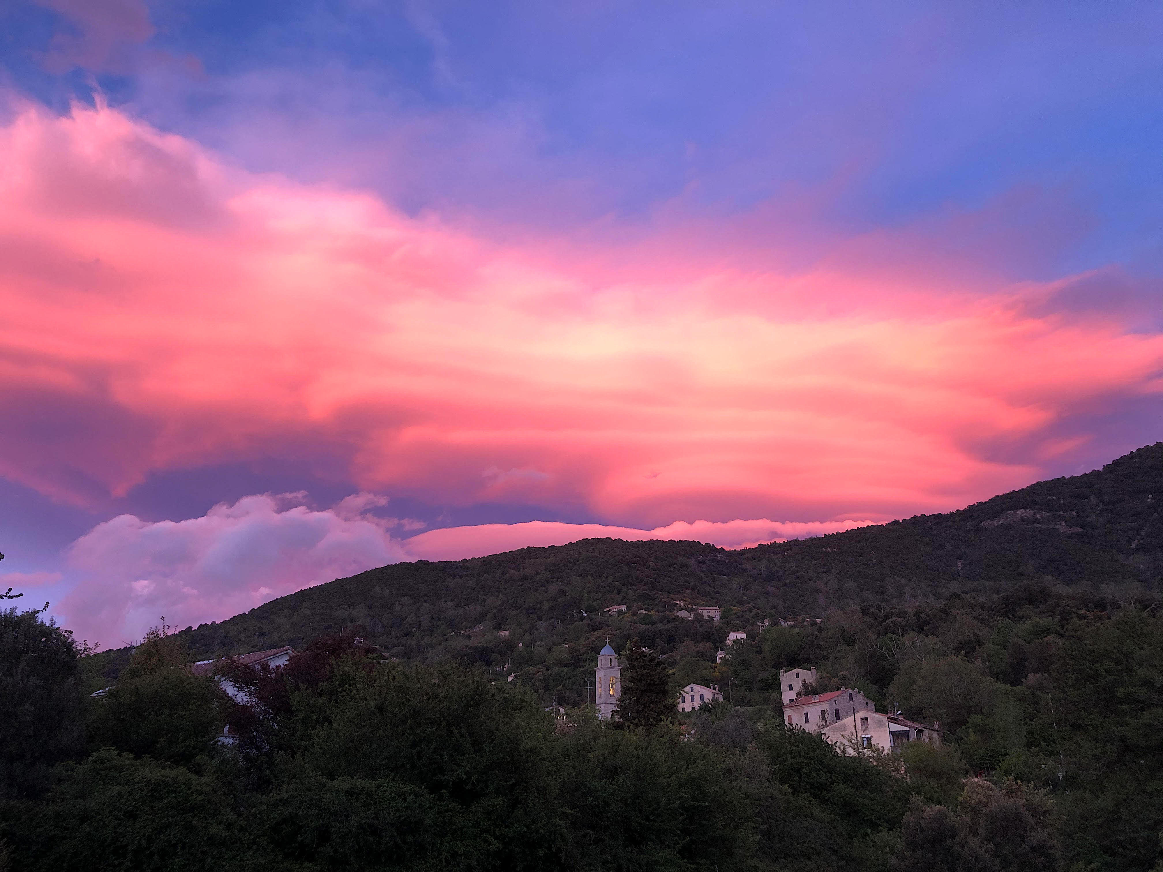 Le coucher de soleil colore les nuages au-dessus du clocher de Tavera en Corse-du-Sud (David Lavergne)