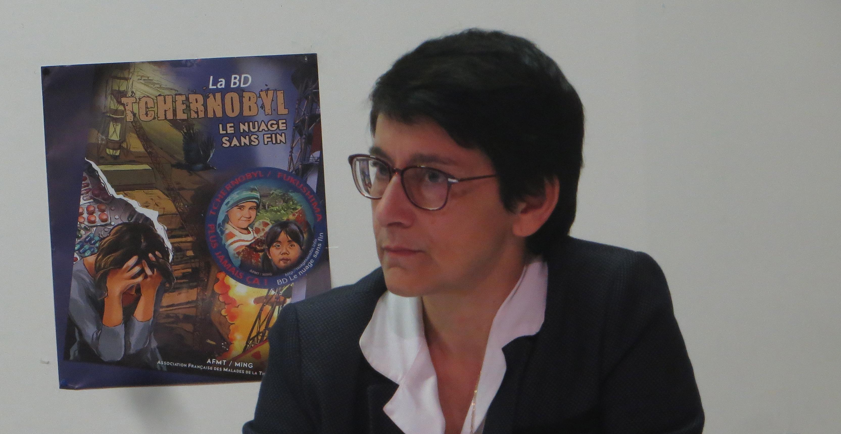 Fabienne Giovannini, conseillère exécutive. Sur le mur, l'affiche de la BD réalisée par l'AFMT avec le soutien du dessinateur MING, pour commémorer les 30 ans de Tchernobyl, en retraçant l'histoire de la catastrophe et ses conséquences sur la santé et sur l'environnement.